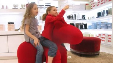 Two girls sit on chair in form of horse also hold balloons — Stock Video