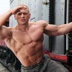 Strong shirtless man keeps watch on locomotive — Stock Photo #7429395