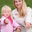Mother and daughter sit on the grass — Stock Photo #7436497