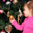 Little girl and christmas fir — Stock Photo #7439965