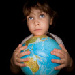 Little girl keeps in hands over globe of world isolated on black — Stock Photo #7938081