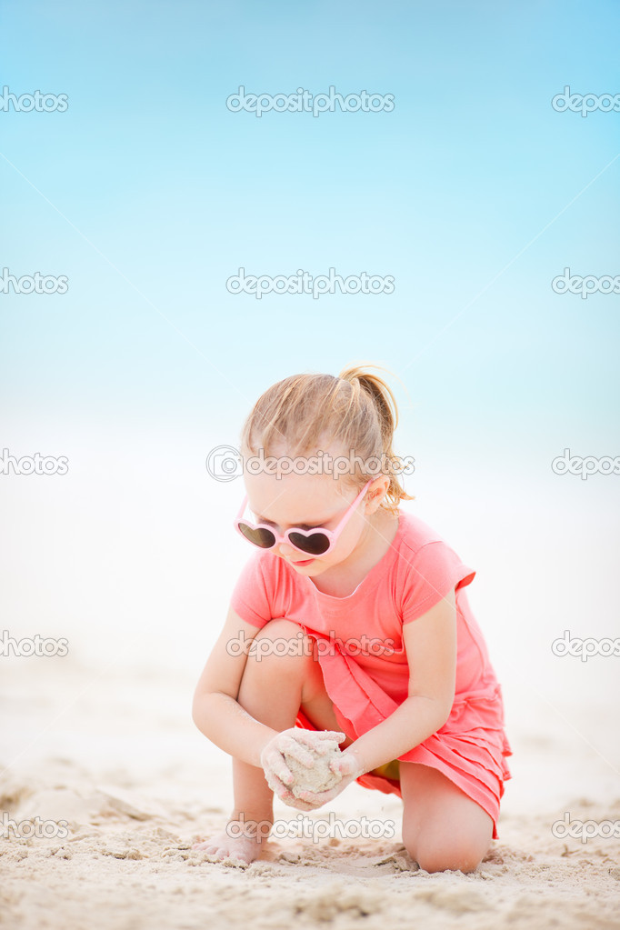 Portrait of adorable little girl at tropical beach playing with sand — Stock Photo #12952435