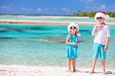 Kids in Santa hats at the beach — Stock Photo
