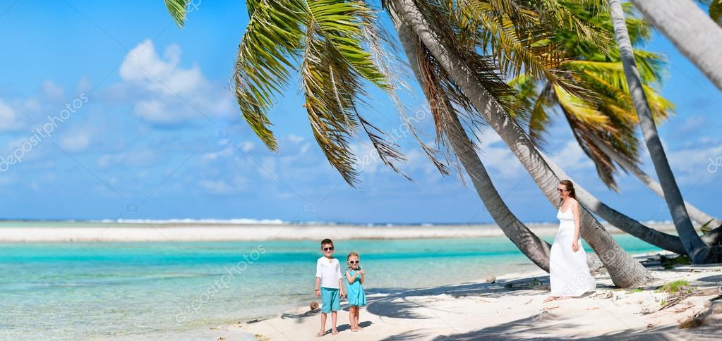 Panoramic photo of beautiful mother and two kids on a deserted island — Stock Photo #13750331