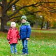 Two kids in an autumn park - Stock Photo
