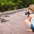 Stock Photo: Little girl photographing iguana