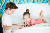 Kids playing on tablet device — Stock Photo