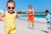 Mother and kids on a Caribbean vacation walking along a beach — Stock Photo