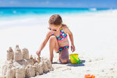 Little girl at tropical beach making sand castle — Stock Photo