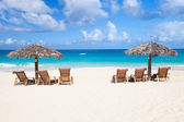 Chairs and umbrellas on tropical beach — Stock Photo
