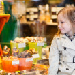 Little girl looking at chocolate in shop — Stok fotoğraf