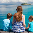 Mother and kids sitting on wooden dock — Stock Photo