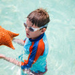 Little boy holding a giant starfish — Stock Photo