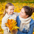 Mother and daughter outdoors at autumn day — Stock Photo
