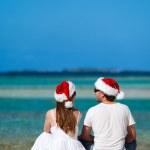 koppel in santa hoeden op strand — Stockfoto