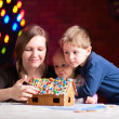 Mother with kids making gingerbread house — Stock Photo #3696605