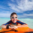 Stock Photo: Boy swimming on boogie board