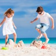 Stock Photo: Two kids crushing sandcastle