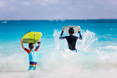 Father and son running with boogie boards — Stock Photo