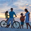 Family with a bike at tropical beach — Stock Photo #44987611