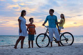 Family with a bike at tropical beach — Stock Photo