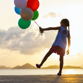 Happy girl with balloons at sunset — Stock fotografie