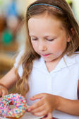 Little girl eating donut — Stock Photo