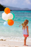 Back view of little girl with balloons at beach — Stock Photo