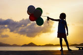 Happy girl with balloons at sunset — ストック写真