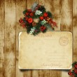 Christmas wreath on the wood door with a Christmas postcard — Stock Photo