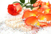 Petals of roses and pearls — Stock Photo