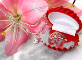 Gold ring and pink lilies — Stock Photo
