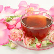 Tea and petals of pink roses — Stock Photo