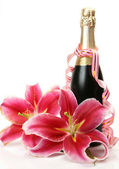 Pink lilies and champagne — Stock Photo