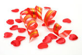 Streamer and red flower petals on white — Stock Photo