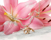Pink lilies and gold ring — Stock Photo