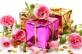 Pink roses and gifts — Stock Photo