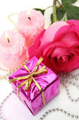 Pink rose and gifts — Stock Photo