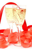 Champagne and petals of roses — Stock Photo