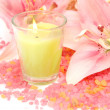 Pink lilies and burning candle — Stock Photo