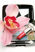 Decorative cosmetics and pink orchid — Stock Photo