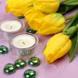 Yellow tulips and burning candles — Stock Photo
