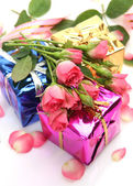 Color boxes and roses — Stock Photo