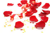 Petals of roses and streamer — Stock Photo