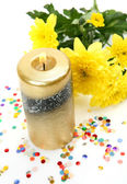 Yellow flowers and candle — Stock Photo