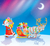 Santa loads Christmas gifts into his sleigh — Zdjęcie stockowe
