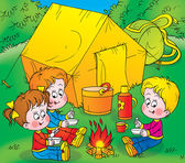 Children warming up by a campfire — Stock Photo