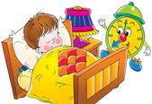 Green alarm clock preparing to wake a sleeping boy — Stock Photo