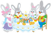 Easter bunnies at the festive table — Stock Vector