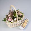 Basket with roses and french macaroons — Stock Photo
